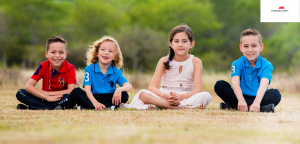 A row of 4 happy children sitting on the grass