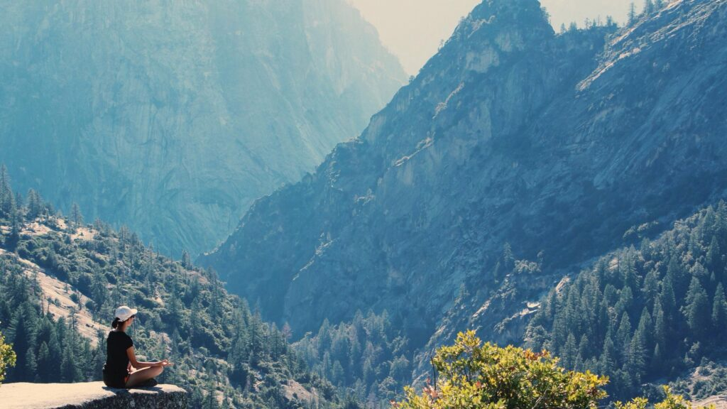 Woman finding happiness meditating on a mountain side.