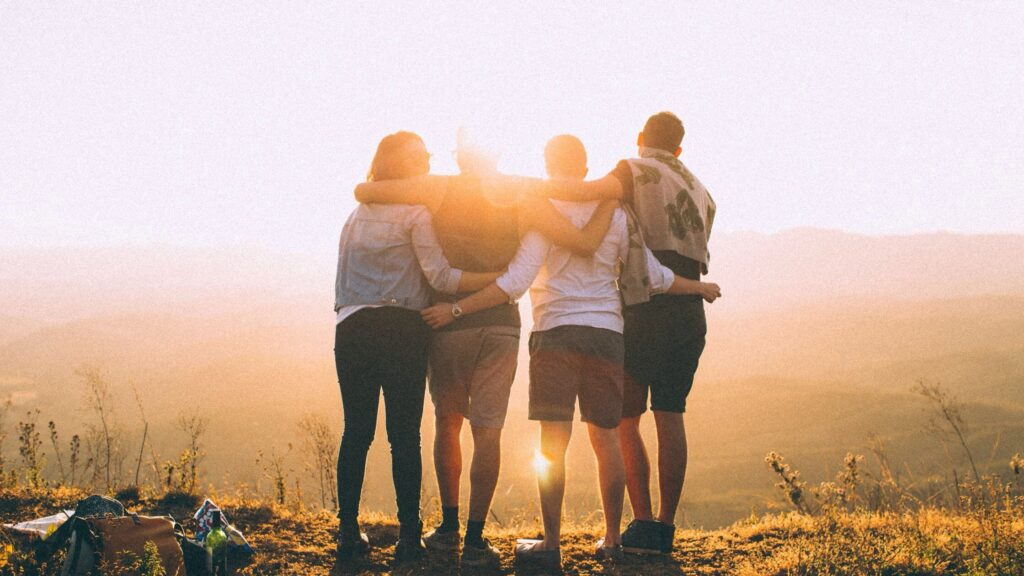 Silhouette of 4 friends hugging and watching the sunset.