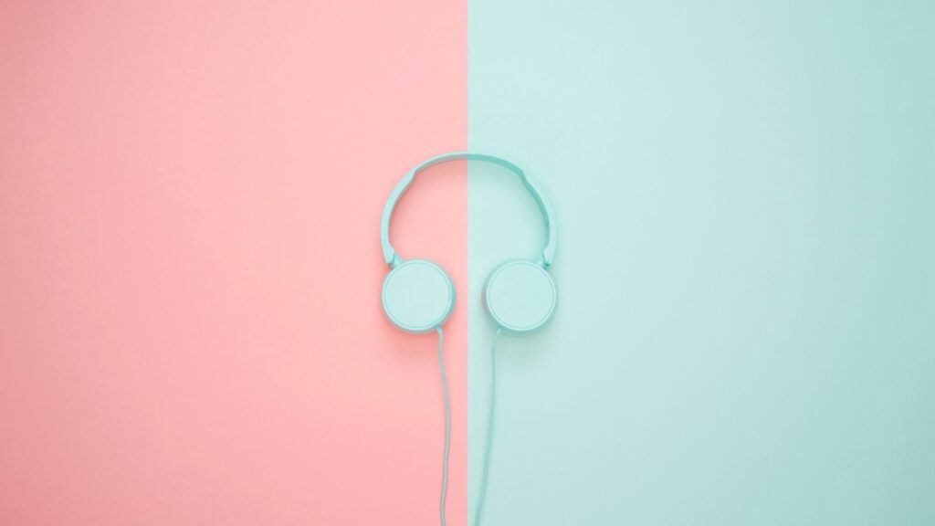 9 of 15 ways your phone can make you happy. Sign up to Audible and listen to books. A set of headphones on a blue and pink background.