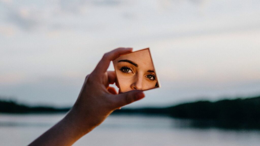 Woman's face reflected in a small mirror