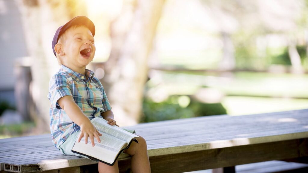A small boy laughing whilst happily holding a complex book.