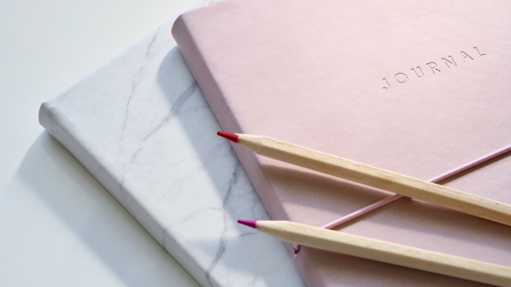 How to choose a happiness journal. A pink and marble journal sit on a white desk with 2 pencils on top.