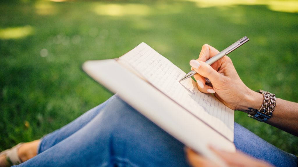 How to choose a happiness journal? Think about where and when you will use it. A woman sits on grass writing in a journal.