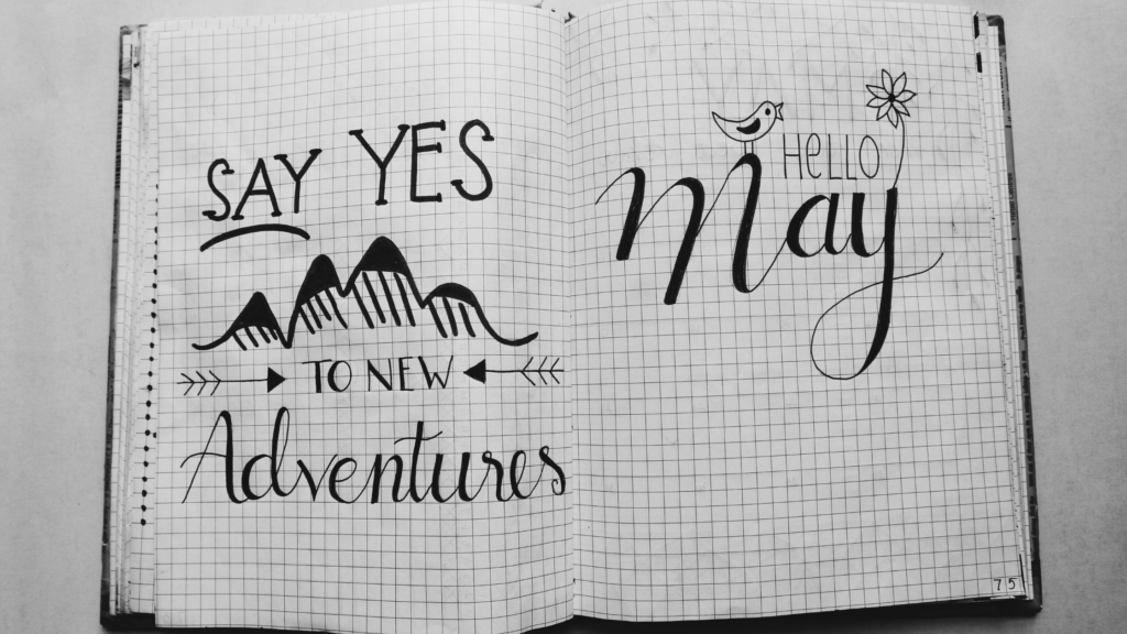 "When choosing a happiness journal consider the interior pages. The inside of a grid ruled journal which reads ""Say Yes to Adventures"" and ""hello May""."