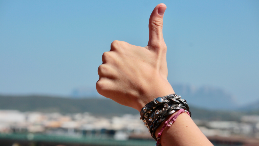 Stay happy on social media by posting positively. Close up of a hand giving the thumbs up against a blue sky.