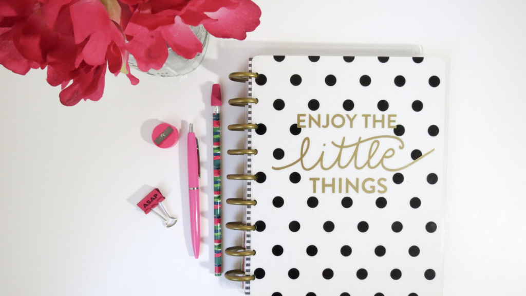 "Choosing the look of your happiness journal is as simple as choosing one you love. A white journal with black polka dots says""Enjoy the little things"" On a white background with pink accessories and flowers"
