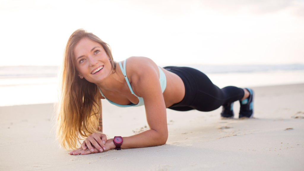 13 of 15 ways your phone can make you happy. Get fit! Use the inbuilt tracker, or one of the many fitness apps to help you. A woman smiles doing a plank on the beach.