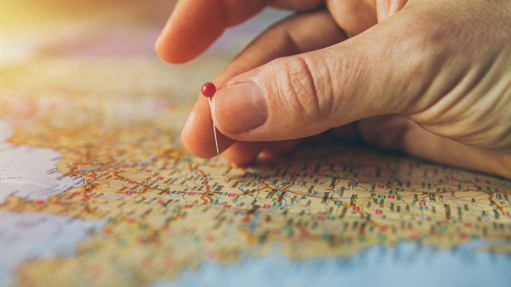14 of 15 ways your phone can make you happy. Go on adventures. Use the geocaching website to go hunting for treasure.  A close up of a person's hand placing a pin in a map.