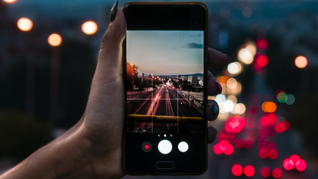 3 of 15 ways your phone can make you happy. Photography. Taking photos on your phone is a fantastic way your phone can make you happy. A woman's hand holds a phone photographing a city road in the evening.