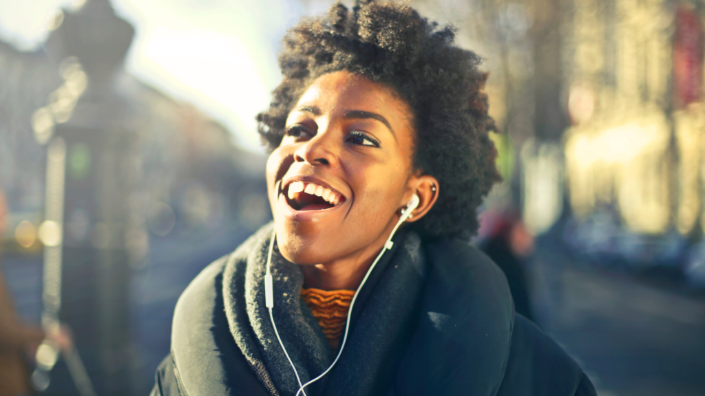 2 of 15 ways your phone can make you happy. Playing music on your phone while walking, jogging, studying or doing chores is a brilliant way your phone can make you happy. A woman appears to be singing and smiling as she listens to music on her phone.