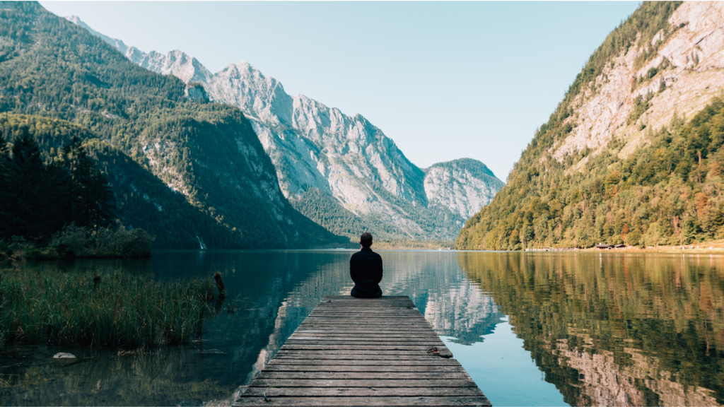 6 of 15 ways your phone can make you happy. Use your phone to make you happy by choosing an app to support your mental health and happiness. A silhouette of a person sitting on the end of a jetty overlooking a beautiful lake and mountain view.