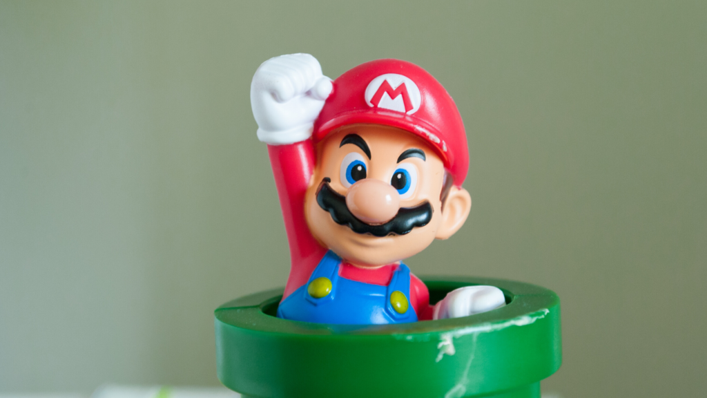 8 of 15 ways your phone can make you happy. Play games. A little figurine of Mario from Super Mario Brothers, in a green pot with his hand in the air.