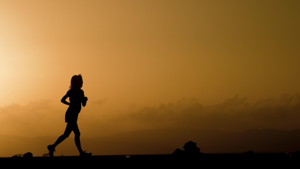 It is easy to exercise for happiness. The silhouette of a person running against an orange sky