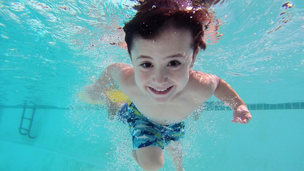It's easy to exercise for happiness. Swim. A child swims under water in a blue pool with his eyes open.