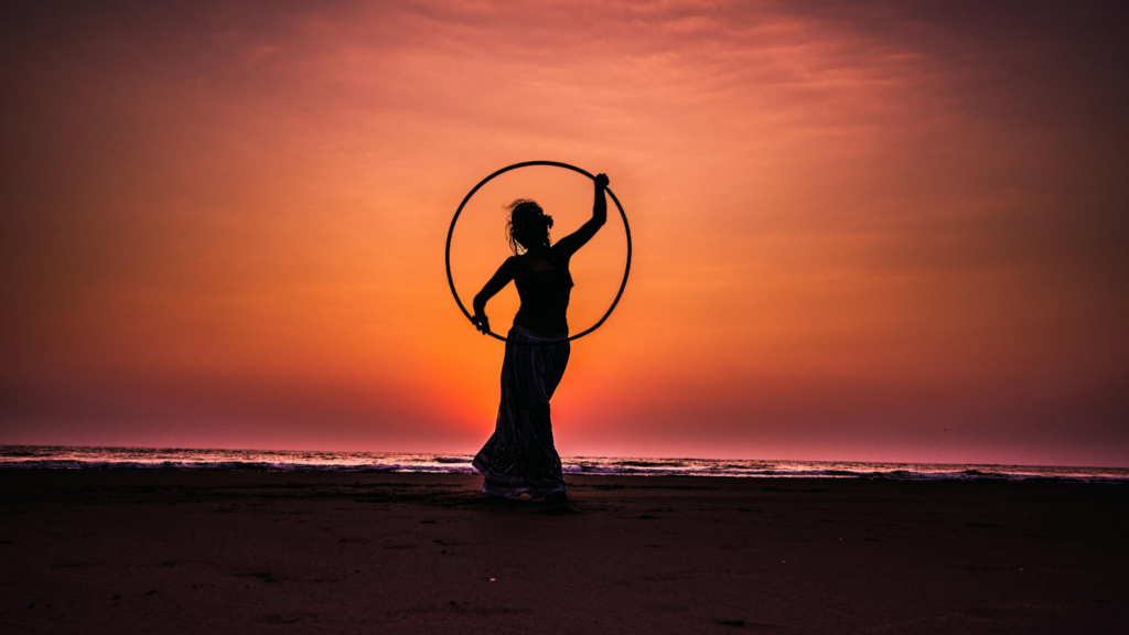 It's easy to exercise for happiness. hula hoop. A silhouette of a woman woman playing with a hula hoop in a beach against a pink sky