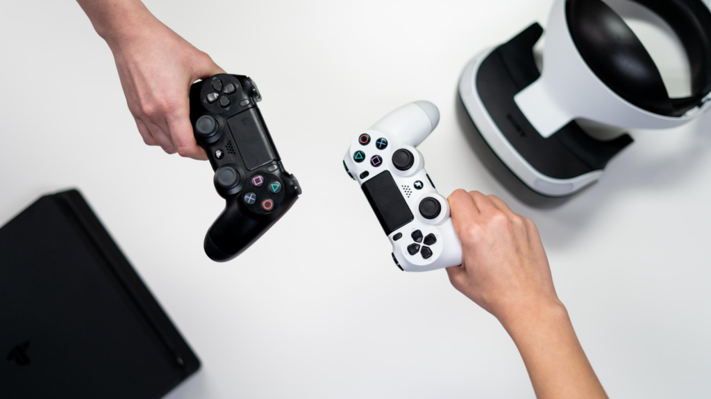 It's easy to exercise for happiness. Use your video games. 2 people hold one black and one white controller on a white background.