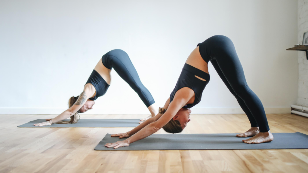 It's easy to exercise for happiness. Yoga. 2 women perform the downward dog pose on black yoga mats on floorboards with a white back wall.