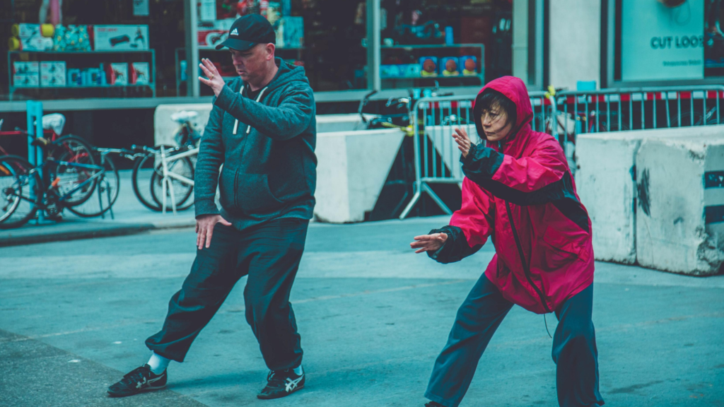 It's easy to exercise for happiness. Try Martial arts. Two people perform Tai chi in a city street.