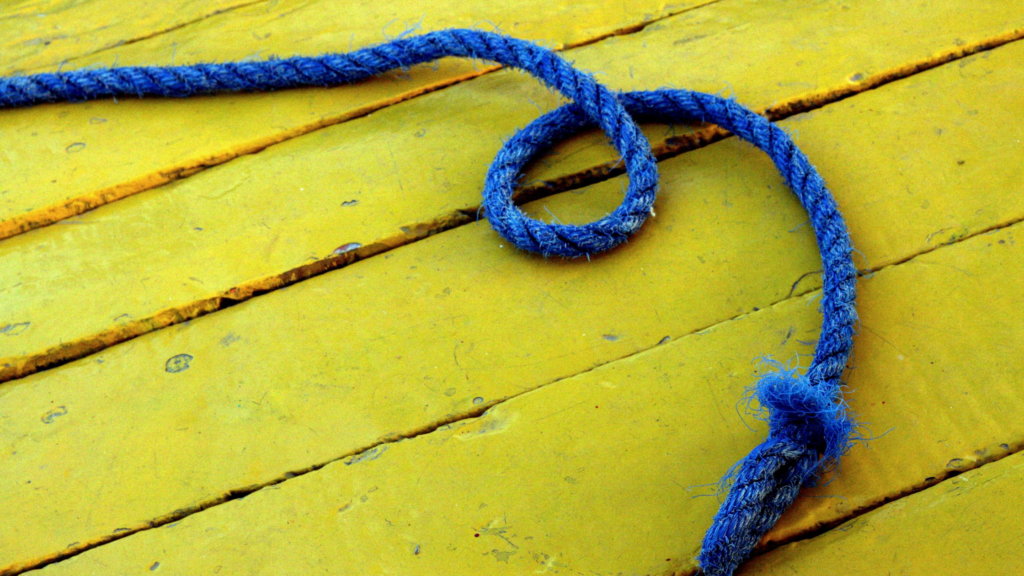 It's easy to find ways to exercise for happiness. Try skipping! A blue rope lies on yellow painted floor boards.