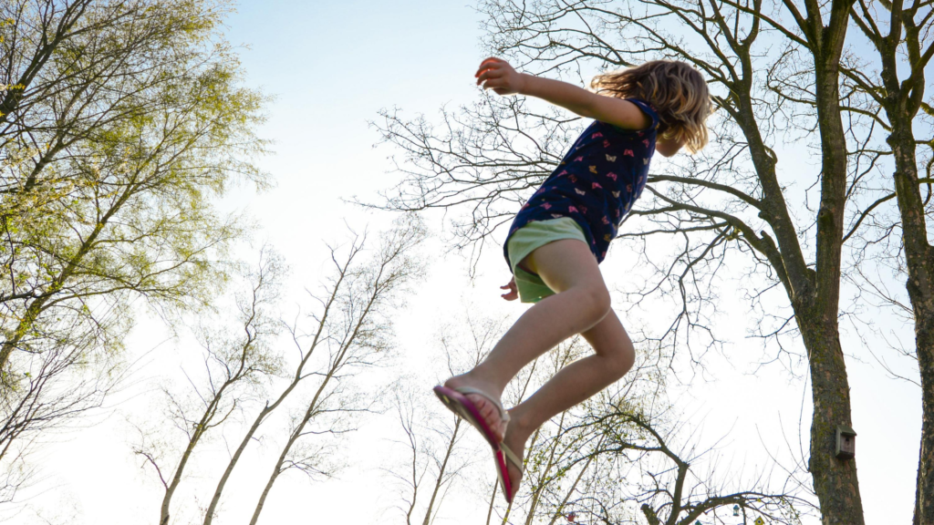 It's easy to exercise for happiness. Bounce on a trampoline. A child bounces high with trees in the background.