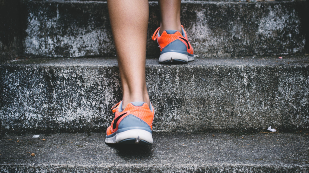 It's easy to exercise for happiness. Climb those stairs. A person's feet and ankles are shown wearing trainers and climbing grey stone steps.