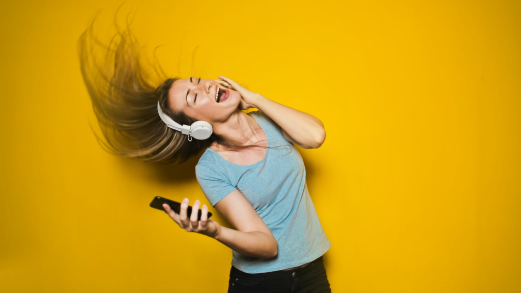 It's easy to exercise for happiness. Dance! A woman wearing headphones dances and sings against a yellow background.