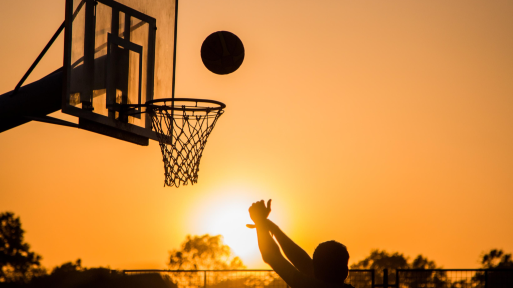 It's easy to exercise for happiness. Play Ball. The silhouette of a person throwing a ball through a basketball hoop against an orange sky.