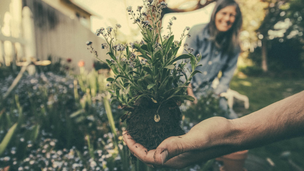It's easy to exercise for happiness. Gardening! A person holds a plant in the foreground while a woman smiles in the background.