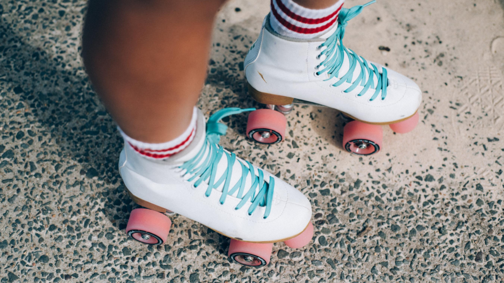 It's easy to exercise for happiness. Roller skates. A person's feet  in their white skates with pink wheels.